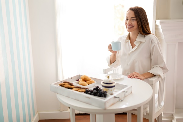 Beautiful smiling Russian woman enjoying her morning cup of tea and having breakfast