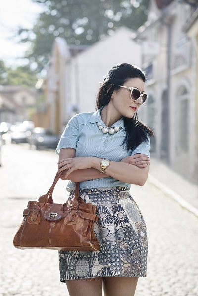 Fashionable dark-haired Russian woman posing with a leather bag watching sideways