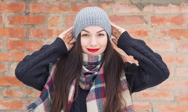 Carefree smiling Russian girl posing for the camera wearing a hat on a winter day