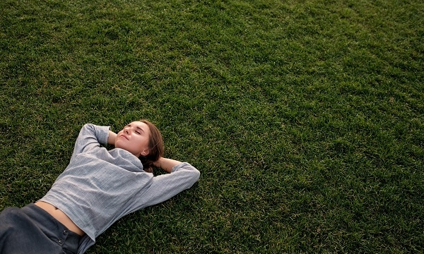 Beautiful young Russian woman lays down on the grass and rests while watching the clouds